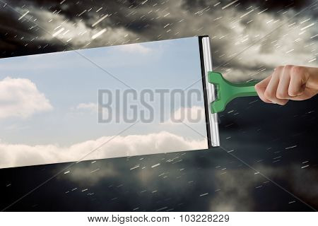 Hand using wiper against cloudy sky with snow falling