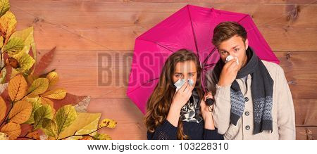 Couple blowing nose while holding umbrella against bleached wooden planks background