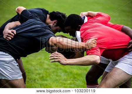 Rugby players doing a scrum at the park