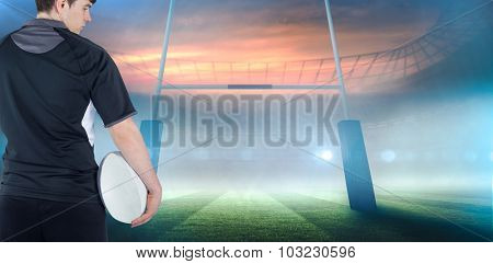 Back turned rugby player holding a ball against rugby stadium