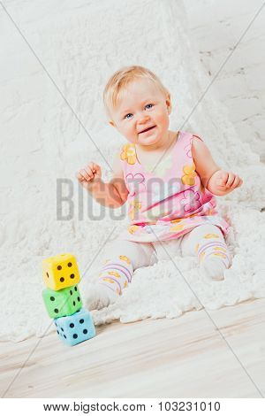 Smiling girl sitting nearby cubes