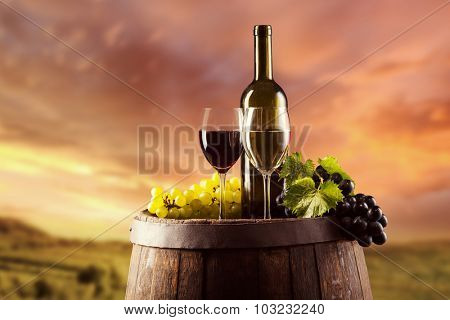 Red and white wine bottle and glass on wooden keg. Vineyard on background
