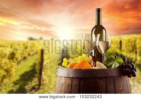 White wine bottle and glass on wooden keg with various kind of cheese. Vineyard on background