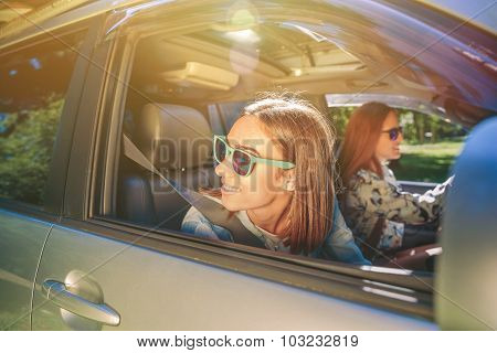 Happy young woman looking back through the window car