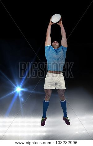 Rugby player catching the ball against spotlights