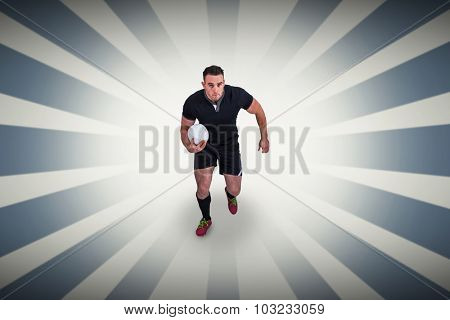 Rugby player running with the ball against linear background