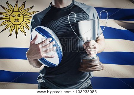 Midsection of successful rugby player holding trophy and ball against close-up of uruguayan flag