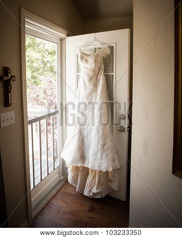 bridal dress hanging on door
