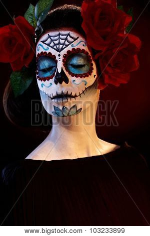 Woman in scary santa muerte mask, eyes closed.