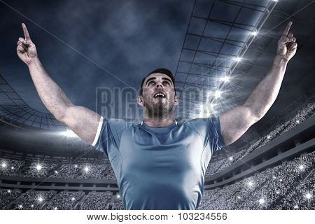 Rugby player cheering and pointing against football stadium