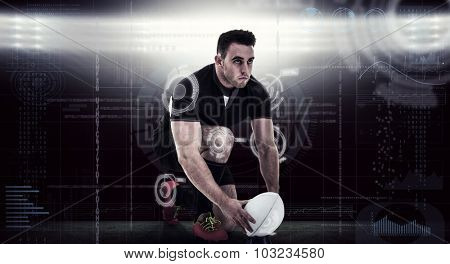 Rugby player getting ready to kick ball against spotlights
