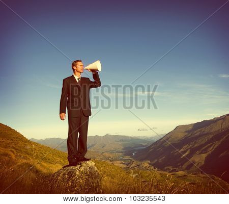 Businessman Shouting on the Top of the Mountain Concept