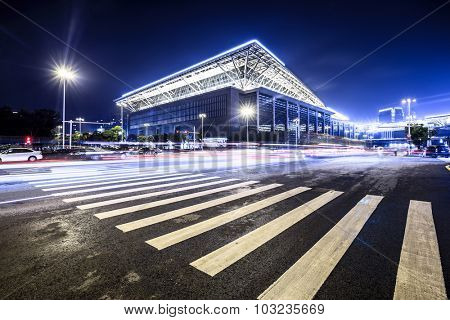 empty road with zebra crossing and gymnasium in modern city at night