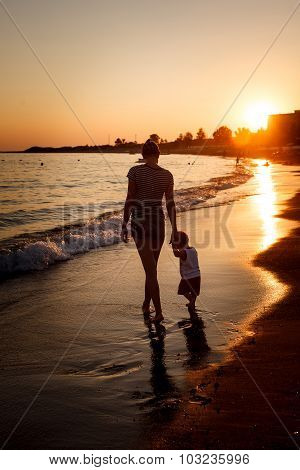 Siluhettes of mother and son by the sea at sunset
