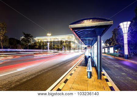 bus station next to a road at night with neon light