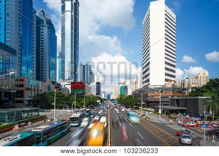 heavy traffic on an asphalt road with skyscrapers aside