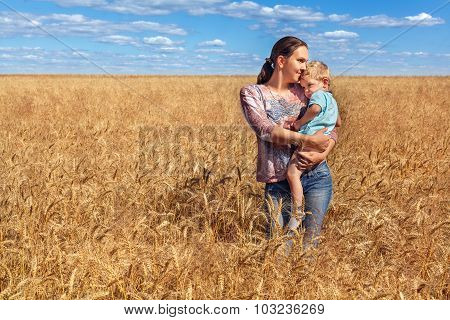 young mother and her son at the wheat field