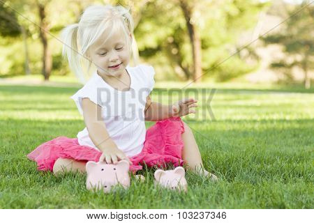 Cute Little Girl Having Fun with Her Large and Small Piggy Banks Outside on the Grass.