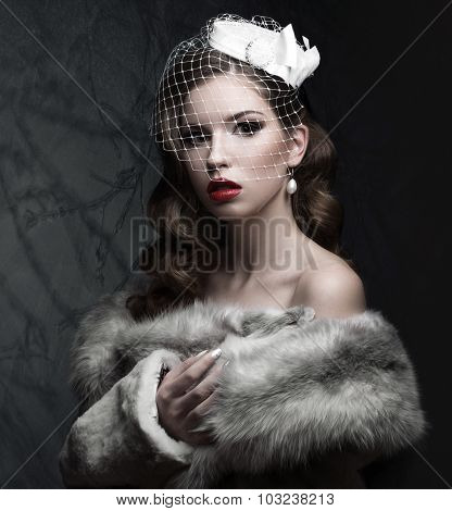 Elegant lady in fur coat with veil and nail Design. Winter image. Beauty face.