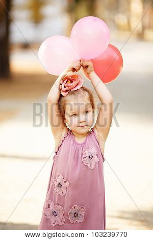 Portrait Of Laughing And Playing Little Girl Holding Colorful Balloons.