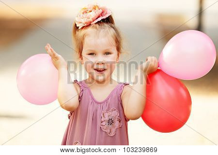 Portrait Of Laughing And Playing Birthday Girl Holding Balloons