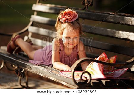 Portrait Of A Little Girl Reading A Children's Book Lying On A Park Bench