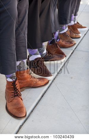 men in tan and brown showes with purple argyle socks