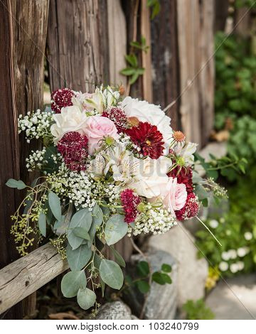 dark red, cream and green bridal bouquet resting on an old wooden fence