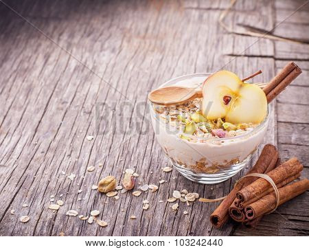 Overnight Oatmeal with yogurt, ground cinnamon and slice of apple in a glass bowl