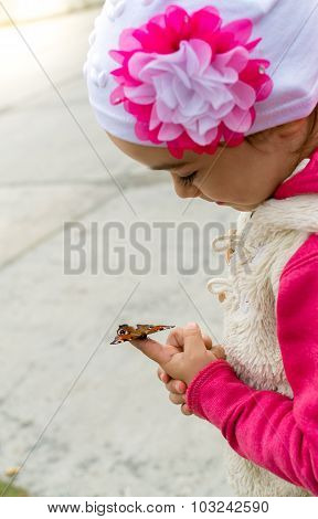 Young Girl Aged 5 Looking At A Butterfly