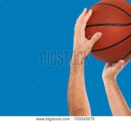 Hands holding a basketball