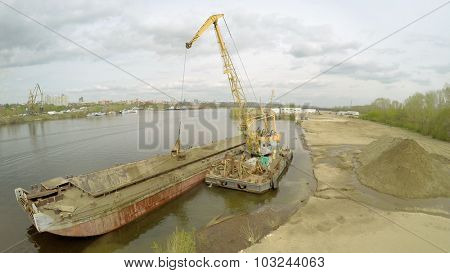 SAMARA - MAY 10, 2015: Crane and barge for sand on shore of Volga river at spring cloudy day. Aerial view video frame