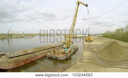 SAMARA - MAY 10, 2015: Crane unloads sand from barge on shore of Volga river at spring cloudy day. Aerial view video frame