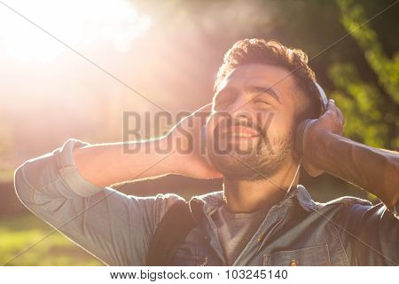 Hipster student man in earphones enjoying sunset