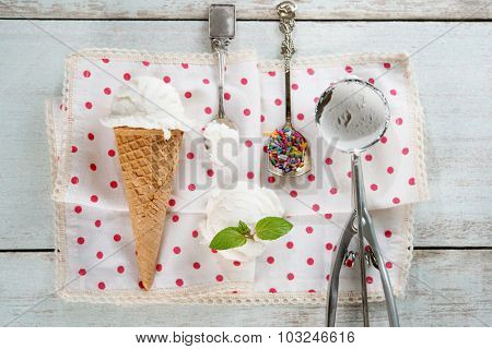 Top view scoop coconut ice cream in waffle cone with utensil, spoon and color rice on wood background.