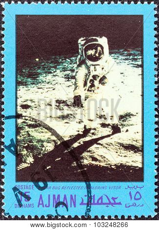 AJMAN EMIRATE - CIRCA 1970: Stamp shows Lunar bug reflected in Aldrin's visor