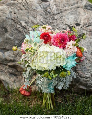 bright and beautiful bridal bouquet of flowers sitting on the grass leaning against a rock
