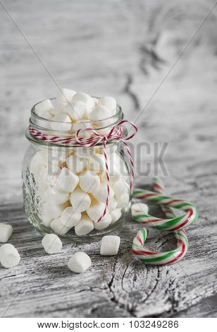 Marshmallows In A Glass Jar And Candy On A Light Wooden Surface, Vintage Style