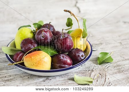 Fresh Plums And Pears On A White Enamel Plate On A Light Background