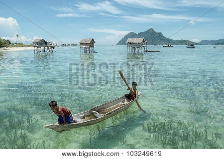Unidentified Borneo Sea Gypsy Kids On A Canoes  In Mabul Maiga Island.