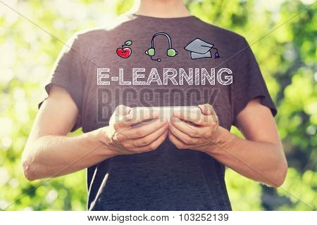 E-learning Concept With Young Man Holding His Smartphone Outside