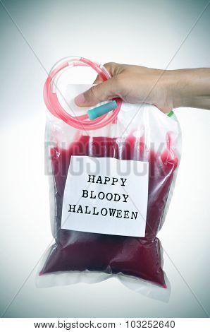closeup of the hand of a young man holding a blood bag with a label with the text happy bloody halloween written in it, with a slight vignette added