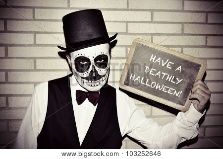 a man with calaveras makeup, wearing bow tie and top hat, against a brick wall, shows a chalkboard with text have a deathly halloween written in it