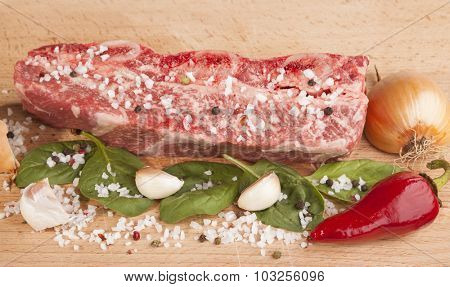 Close-up piece of fresh marbled beef, chili pepper, parsley, onion, garlic, ribs lie on a wooden tray.