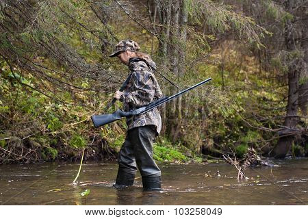 Woman Hunter In Waders Crossing The River