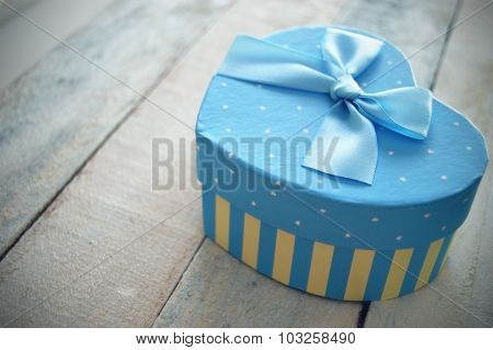 Heart shaped gift box decorated with a blue ribbon