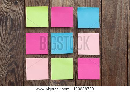 Multicolored paper stickers note on wooden background.