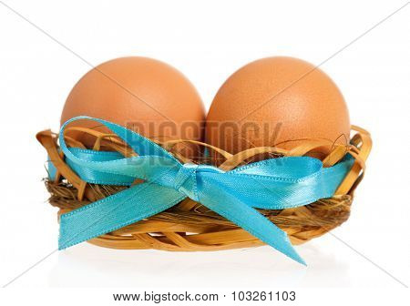 Fresh eggs in the nest with bow, isolated on white background
