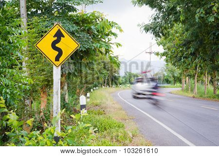 Winding Road Sign In The Forest With Blurred Car And Motorcycle