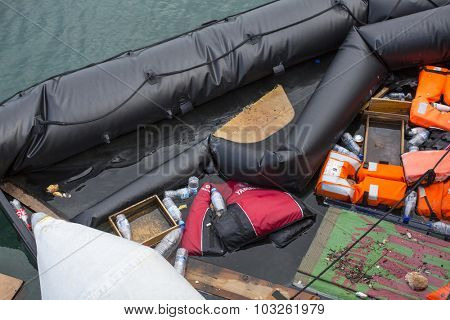 KOS, GREECE - SEP 28, 2015: Life Jackets discarded and sunken Turkish boat in the port. Kos island is located just 4 kilometers from the Turkish coast, and many refugees come from Turkey in an boats.
